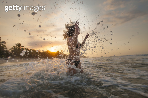 A woman plays in the waves at Palomino on the Caribbean coast of Colombia - gettyimageskorea