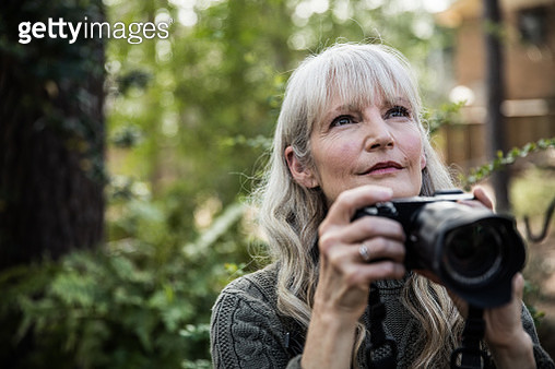 Woman taking nature photographs outdoors - gettyimageskorea