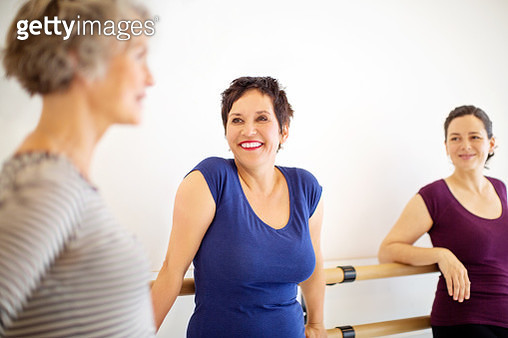 Group of females talking in dance studio during break. Women discussing while standing at health club. - gettyimageskorea