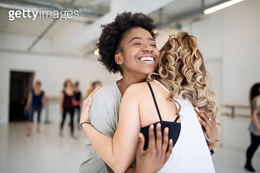 Dance instructor greeting students at fitness studio. Women at dance class meeting and greeting each other. - gettyimageskorea
