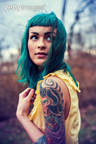 Girl with blue hair and tattoos looking over - gettyimageskorea