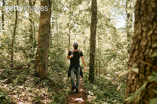 Young man walking through a forest in a National Park after Coronavirus pandemic. - gettyimageskorea