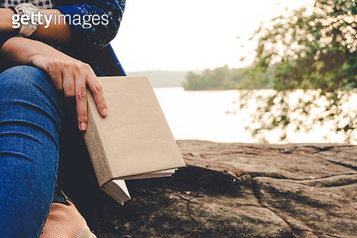 Midsection Of Woman Holding Book While Sitting At Lakeshore Against Sky - gettyimageskorea