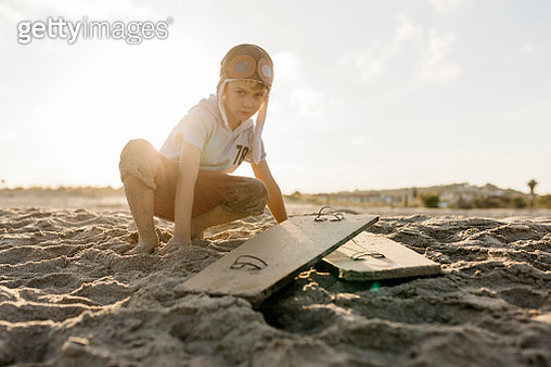 Boy with aviator's cap crouching by aircraft wings on beach - gettyimageskorea