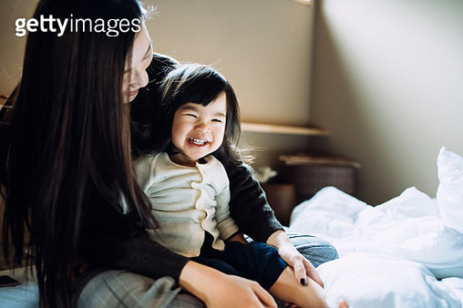 Cute little daughter smiling joyfully and sitting on mother's lap after waking up in the morning - gettyimageskorea