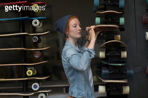Woman working in skateboard shop, organising skateboard display - gettyimageskorea