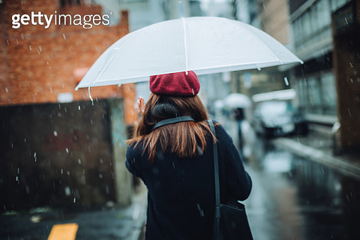 Rear view of woman carrying umbrella walking in the snow in city - gettyimageskorea