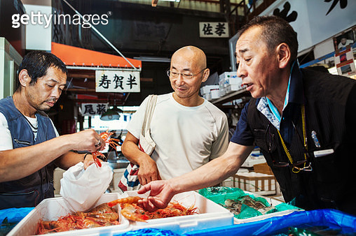 A traditional fresh fish market in Tokyo. Two people selecting shellfish for a customer to buy, filling a bag from boxes of prawns. - gettyimageskorea