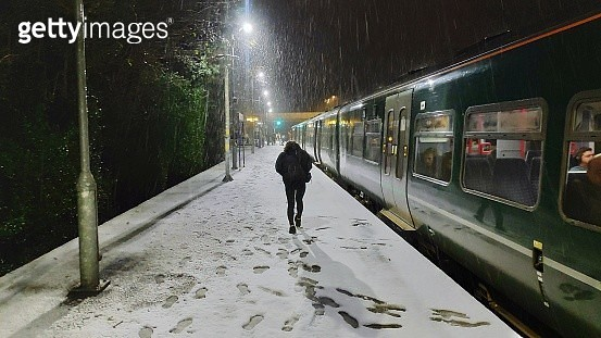 Rear View Of Young Woman Walking On Snow Covered Railroad Station At Night - gettyimageskorea