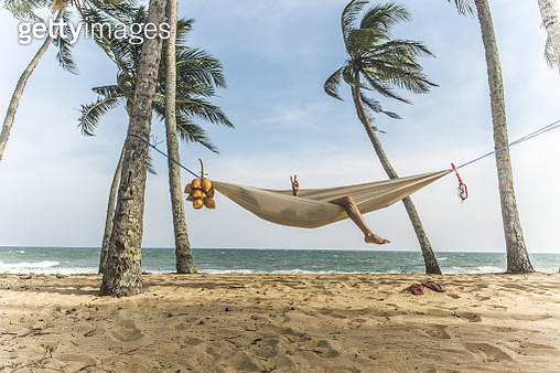 Man relaxing in hammock. - gettyimageskorea