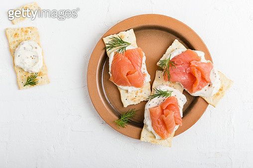Crackers with smoked salmon and mustard sour cream dip, appetizer canapes on rustic ceramic plate viewed from above - gettyimageskorea