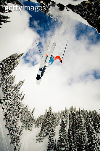 Skier Jumping off Cliff Surrounded by Trees - gettyimageskorea