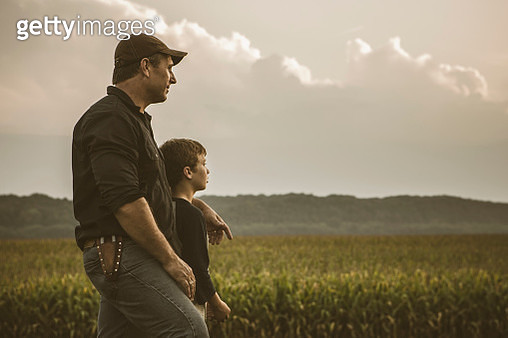 Caucasian father and son overlooking crop fields - gettyimageskorea