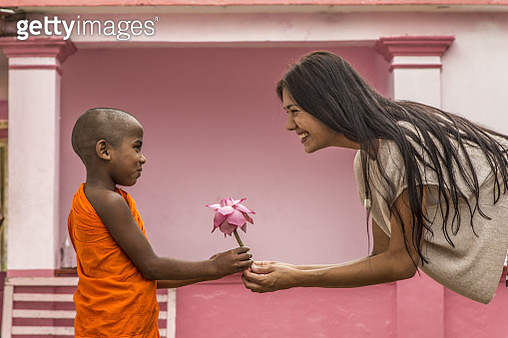 Young Buddhist monk giving lotus flower to young woman tourist - gettyimageskorea