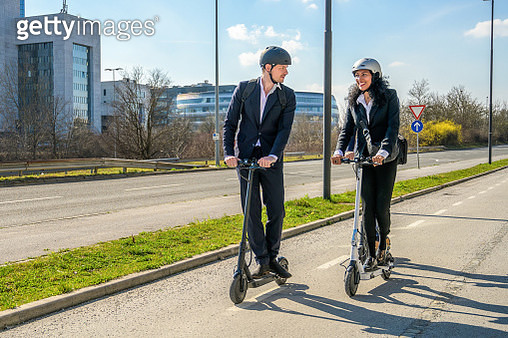 Business people riding electric scooters - gettyimageskorea