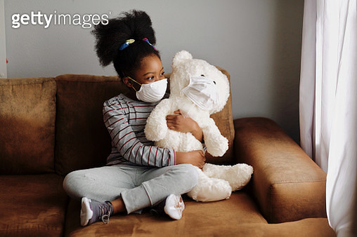 Beautiful young girl holding teddy bear on couch - gettyimageskorea