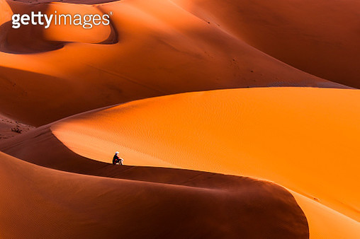Man sitting on top of a giant dune contemplating the sunset, Namibia - gettyimageskorea