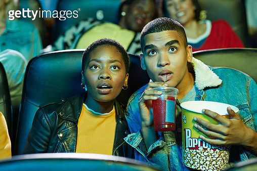 Surprised young man drinking soda while watching movie with friend in cinema hall - gettyimageskorea