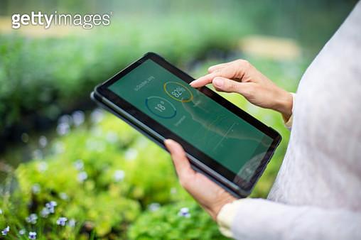 Gardener using digital tablet for information about new plants - gettyimageskorea