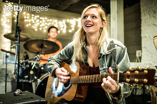 Young woman playing acoustic guitar at band rehearsal - gettyimageskorea