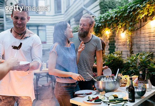 A young couple having a barbecue with friends looking at eachother fondly as they snack. - gettyimageskorea