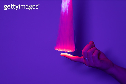 Hand touching red optical fiber - gettyimageskorea
