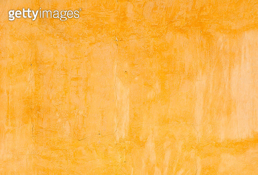 Ochre colored cracked painted wall in bright sunlight in autumn. - gettyimageskorea