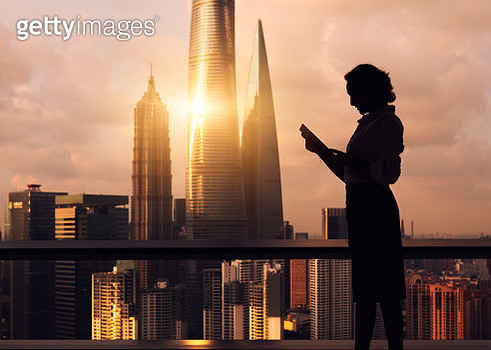 Beautiful Asian businesswoman working near the window, the background is skyscrapers and landmarks of Shanghai, including Shanghai Tower, Shanghai World Financial Center and Jin Mao Tower. - gettyimageskorea