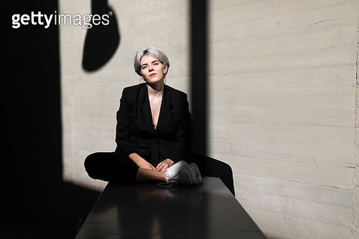 Stylish businesswoman wearing elegant suit relaxing on retaining wall with sunlight and shadow in background - gettyimageskorea