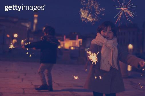 Siblings playing sparklers & fireworks background - gettyimageskorea