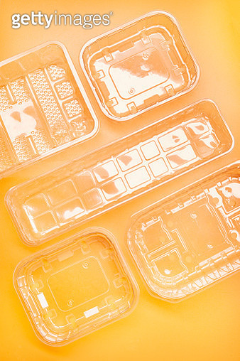 Plastic packaging and transparent garbage on orange colored background, directly above shot - gettyimageskorea