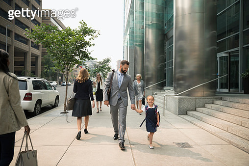 Businessman father and schoolgirl daughter holding hands and walking on urban sidewalk - gettyimageskorea