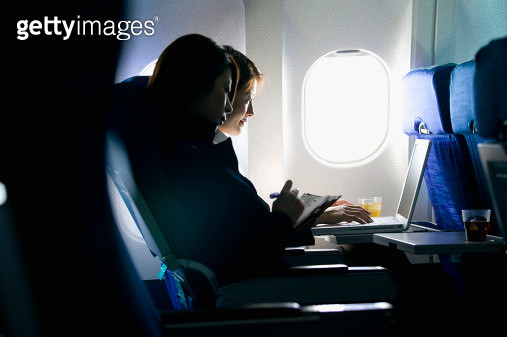 Two young businesswomen sitting in airplane, working on laptop - gettyimageskorea