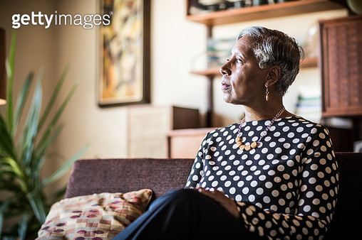 Portrait of woman (60yrs) sitting on couch at home - gettyimageskorea