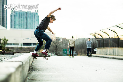 Young men skateboarding in urban environment. - gettyimageskorea