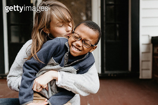 A mother and her adopted son smiling, laughing and cuddling on the front porch in buffalo new york in november - gettyimageskorea