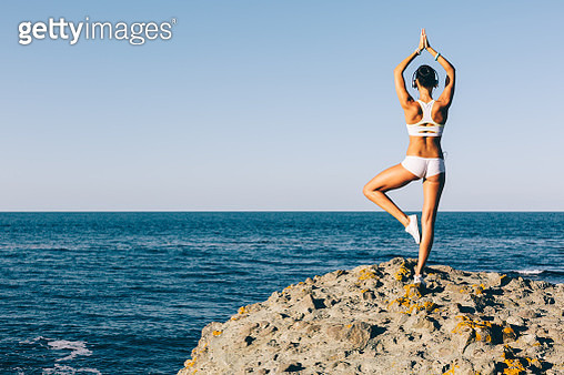 Sports woman meditating at the beach - gettyimageskorea