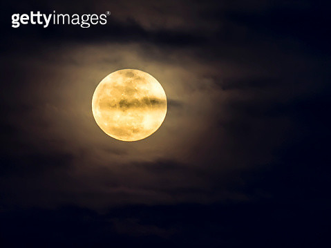 Full frame of the Supermoon of yellow color on a black sky with some high clouds. Valencia, Spain - gettyimageskorea