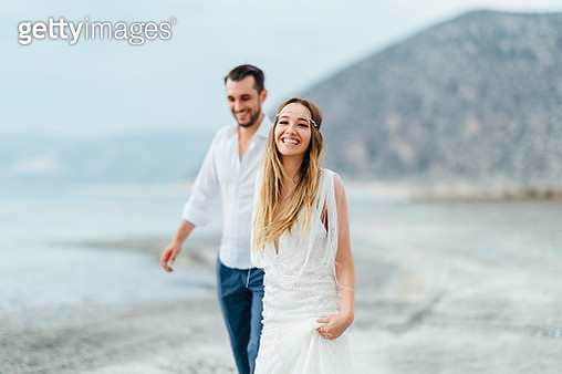 A young couple is walking happily by the water hand in hand. - gettyimageskorea