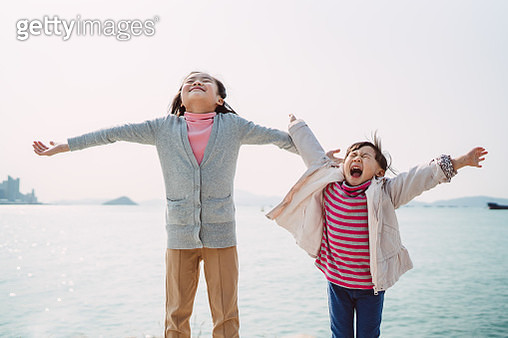 Little sisters reaching their arms to sky joyfully in promenade - gettyimageskorea