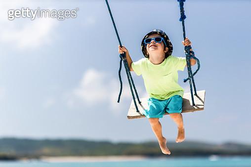 Cute little boy having fun on a swing in summer day at beach. Copy space. - gettyimageskorea