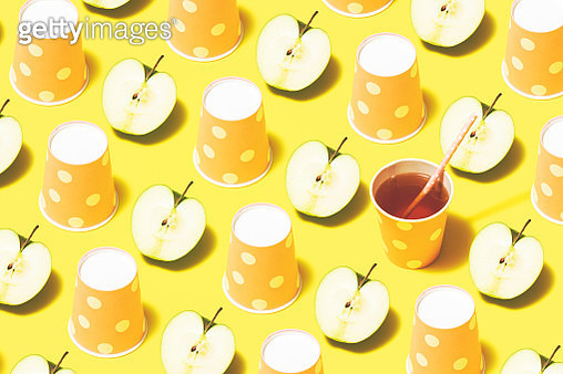 Disposable paper cups on color background flat lay. Apple juice and pink polka dot paper cups flat lay on yellow background - gettyimageskorea