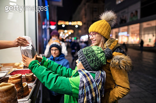 Kids buying at the Czech street bar.  Brothers and sister are buying traditional fresh baked cake - Czech Trdelnik. Brno old town, Czech Republic.Nikon D850 - gettyimageskorea