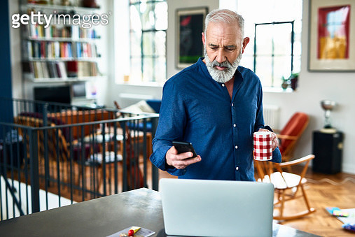Man in his 50s in apartment, texting, with laptop on work surface, serious expression on face, planning for the day ahead, drinking coffee - gettyimageskorea