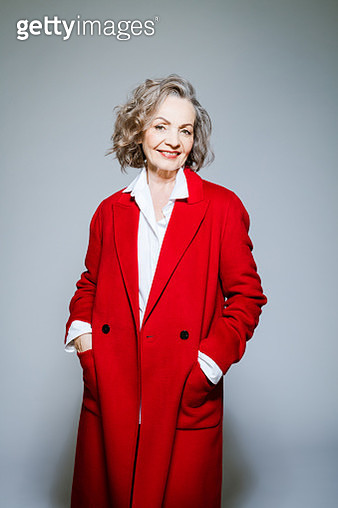 Elderly lady wearing red coat and white shirt standing with hands in pockets against grey background, smiling at camera. Studio shot of female designer. - gettyimageskorea
