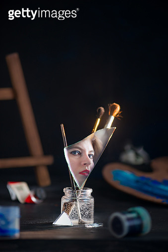 Self portrait concept with reflection, a mirror shard among paint brushes, young female artist with red lipstic - gettyimageskorea
