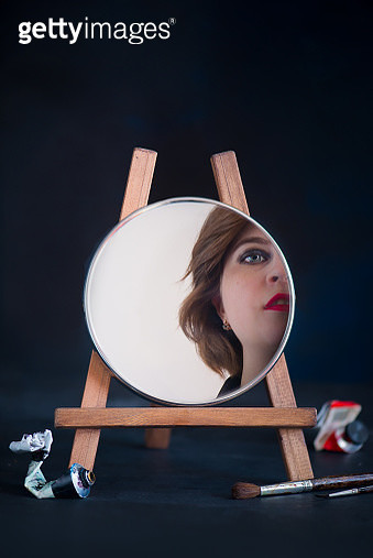 Self portrait concept with reflection, a mirror on a wooden easel, young female artist with red lipstic - gettyimageskorea