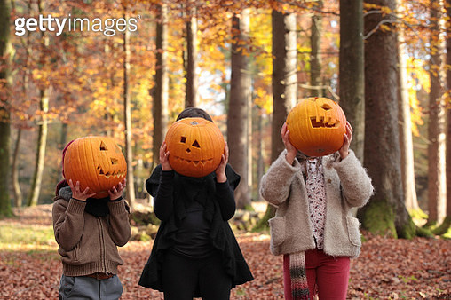 Two girls and a boy are playing halloween in the woods, covering their faces with carved pumpkins. - gettyimageskorea