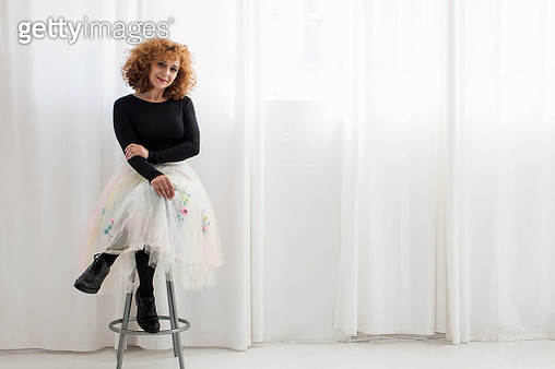 Portrait of woman sitting on stool looking at camera - gettyimageskorea