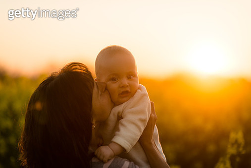 Young mother kissing her tot. Nature background. - gettyimageskorea